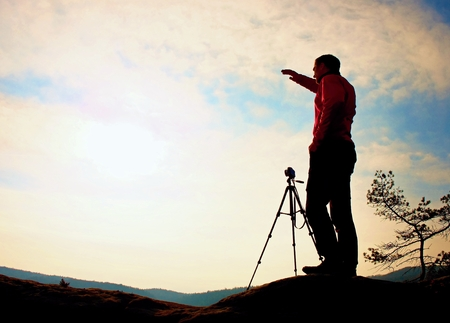 Nature photographer with tripod on cliff and thinking. Dreamy fogy landscape, orange misty sunrise in a beautiful valley below