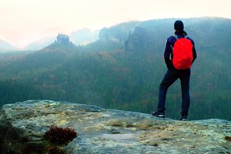 Wanderer mit roten Rucksack auf scharfen Sandsteinfelsen in Fels Reiche Park und wacht über den nebligen und nebligen Frühlings Tal zu Horizont. Standard-Bild - 80485408