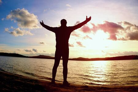 Sportsman standi on beach in warm sporty clothing at sunset. Autumn weather, end of season. Stock Photo