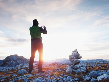 Alone hiker takes phone photo in mountains. Man on Alps mountain peak.View to purple sky above deep foggy valley. Mountains increased from humidity