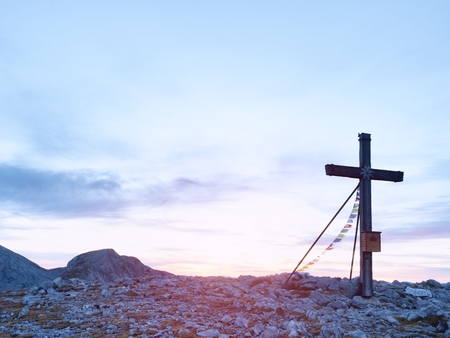 Praying flags fluttering  in the wind on the summit cross. Wooden crucifix on top of Alpine mountain,  in the Dolomite Alps Stock Photo