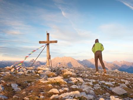 Alone man climber near the summit cross on peak, Dolomite Alps, Austria. Sunny windy evening, great visibility