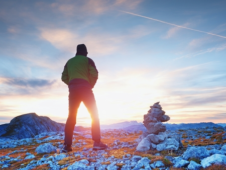 Tourist guide at stocked stones on Alps peak. Strong hiker enjoy sunset in   Alpine mountain. Alone man on few days trek Stock Photo