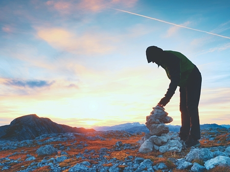 Man hiker is building pebbles pyramid. Stones on Alps mountain summit. Daybreak horizon above blue foggy valley.