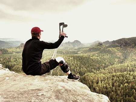 Tired tourist with medicine crutch  and broken leg fixed in immobilizer resting on  mountain summit. Valley bellow sitting man in black sweatshirt and red baseball cap. Sharp sandstone edge.