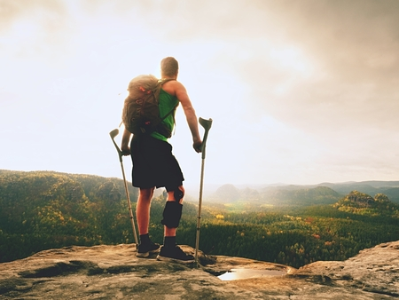 Man with a crutches and broken leg fixed in knee brace feature.Traveler with hurt leg in bandages stay on rocky  view point in mountains.  Hiker with broken leg in immobilizer. Stock Photo
