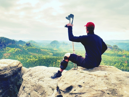 Tired hurt tourist with medicine crutches. Man with  broken leg in knee brace features resting on  exposed rocky summit. Valley bellow sitting man in black sweatshirt and red baseball cap. Sharp sandstone edge. Stock Photo