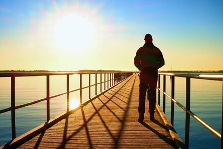 Man silhouette walk on wharf construction above sea to Sun. Fantastic morning with clear sky, smooth water level
