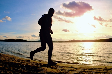 Tall man with sunglass and dark cap is  running on the beach at sunset