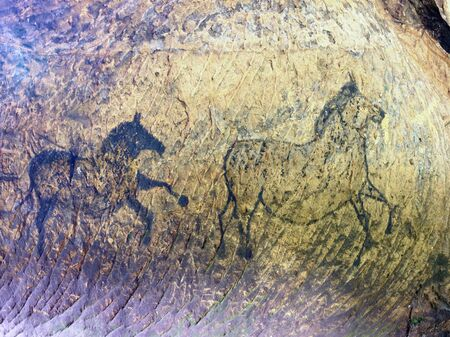 Abstract children art in sandstone cave. Black carbon paint of horses on sandstone wall, copy of prehistoric picture.