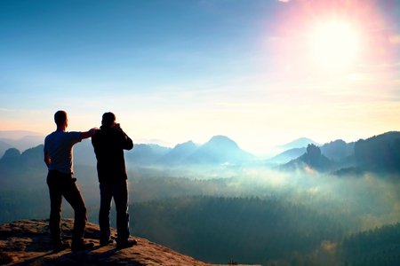 Hiker and photo enthusiast stay on cliff and thinking. Dreamy fogy landscape, blue misty sunrise in a beautiful valley below