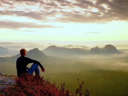 Tall hiker in dark shirt sit on a rockatn heather bushes, enjoy foggy  scenery Standard-Bild