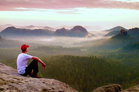 Adult sportsman in white shirt, dark trousars and red cap. Man sit on sharp cliff above valley in rocky mountains park and watch into landscape