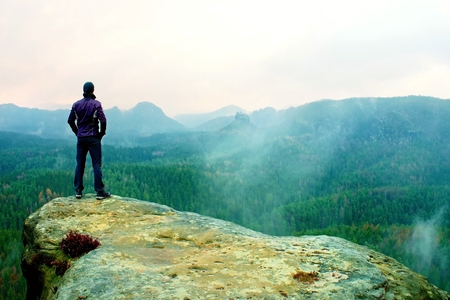 Man stands on the sandstone rock overlooking the valley to Sun. Beautiful moment