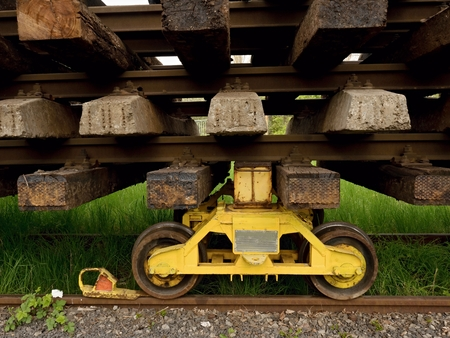 Wagon with old railways. Concrete and wooden sleepers extracted  with rail rods in railway station stock waiting for transport to steel foundry for recycling. Stock Photo