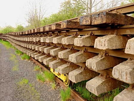 carreta madera: Wagon with extracted old railways. Concrete and wooden sleepers with rail rods in railway station stock waiting for transport to steel foundry for recycling.