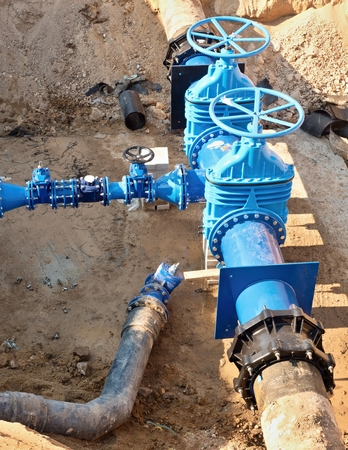 Oil, gas, water industry. Wellhead with valve armature underground. Dug deep trench utilities engineering urban systems.
