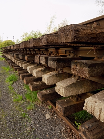 extracted: Wagon with extracted old railways. Concrete and wooden sleepers with rail rods in railway station stock waiting for transport to steel foundry for recycling.