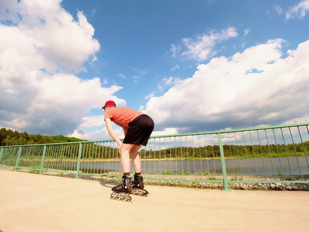 road shoulder: Rear view to inline skater in red t-shirt and black pants skating on the bridge . Outdoor inline skating on smooth concrete ground on lake bridge. Light skin man in four wheel boots