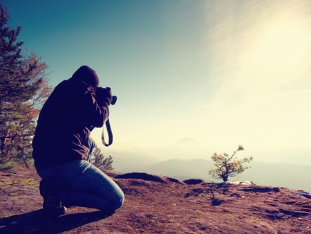 documenting: Photographer  look down into fogy valley. Man is kneeling on cliff and takes photos. Dreamy fogy landscape, blue misty sunrise in a beautiful valley below