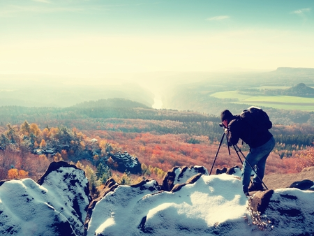 documenting: Professional on cliff. Nature photographer takes photos with mirror camera on snowy rock. Dreamy fogy landscape, spring orange pink misty sunrise in a beautiful valley below.  Stock Photo