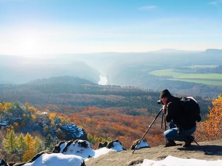 Berufsfotograf macht Fotos mit Spiegelkamera und Stativ auf schneebedeckter Spitze. Träumerische fogy Landschaft, orange nebligen Sonnenaufgang des Frühlinges rosa im schönen Tal unten. Standard-Bild - 81072444