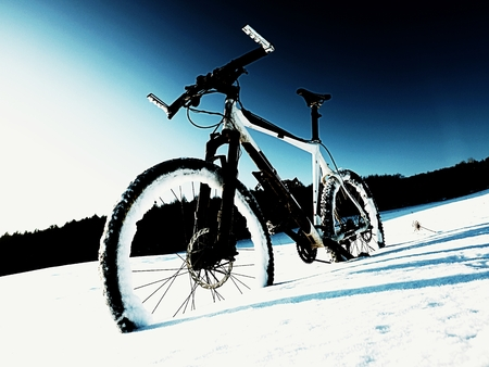 winter road: Extremme contrast. Mountain bike stay in powder snow. Lost path  in deep snowdrift. Rear wheel detail. Snow flakes melting on dark off road tyre.  Winter weather in the field.
