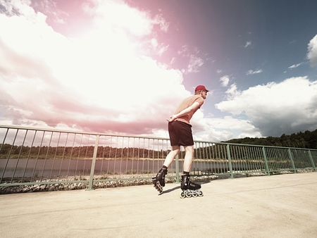 tilting: Middle age man in red t-shirt  with inline skates ride in summer park, popular outdoor roller skating. Sea bridge with blue sky in backgrround