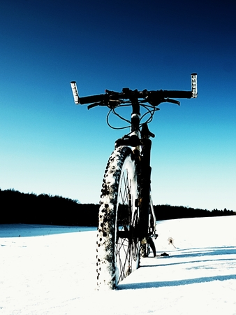 hard disk: Extremme contrast. Mountain bike stay in powder snow. Lost path  in deep snowdrift. Rear wheel detail. Snow flakes melting on dark off road tyre.  Winter weather in the field.