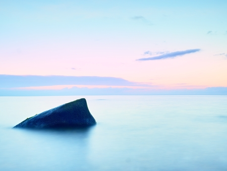 Bizzare stones on costline, the stony beach ends in smooth water of blurred ocean. Colorful sky above