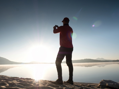 Alone man at the seaside using cell phone to take selfie photo with the beach and sea behind him Stock Photo