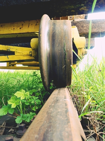 Cargo wagon wheel stay on rusty railway. Old railway wagon wait in depot. Fresh green grass around rail rods Stock Photo