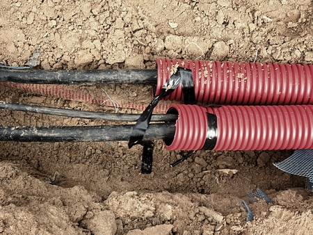 Excavation of trench  with black cables in protective HDPE tube. Lines of metallic and fiber optic cables, building of communication optical network. The installation of connection. Stockfoto