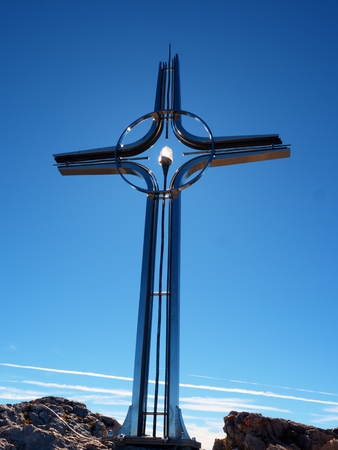 Steel cross raised  at mountain summit  in Alps. Sharp peak. Daybreak Sun in sky. Steel crucifix in memory of victims of mountains. Stock Photo