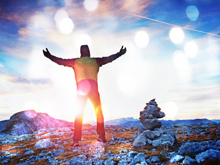 Film grain effect. Film scratch. Happy hiker with raised arms in the wind.  Tourist guide at stocked stones on Alps peak. Strong hiker enjoy sunset in   Alpine mountain. Stock Photo