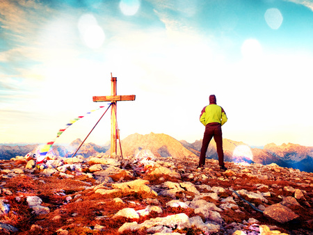 Film grain effect. Film scratch. Man walk along the wooden cross at a mountain peak built to Alps victiims. Cross on top of a mountain peak as typical in the Alps. Stock Photo