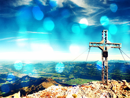Film grain effect. Film scratch. Steel cross raised  at mountain summit  in Alps. Sharp peak. Daybreak Sun in sky. Steel crucifix in memory of victims of mountains.