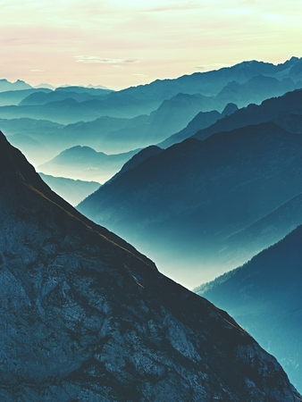 awaking: Spectacular aerial view of mountain silhouettes and misty valleys. Misty awaking of beautiful fairy valley. Peaks of rocks cut creamy foggy clouds. Stock Photo