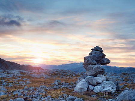 Pebbles pyramid. Stones on Alpine gravel mountain summit. Daybreak horizon above blue foggy valley. Allps mountains increased from humidity