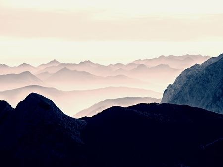 Contours of sharp mountains,  side by side increased from morning high humidity. Far view to daybreak horizon Stock Photo