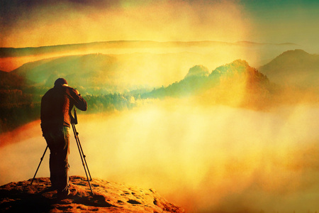 Film grain effect.  Professional on cliff. Nature photographer takes photos with mirror camera on peak of rock. Dreamy fogy landscape Stock Photo