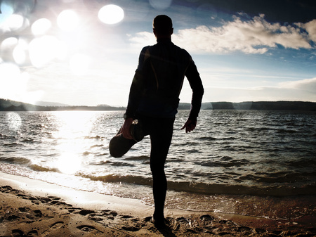 Film grain effect. Silhouette of person in sportswear and short hair on beach seeing into morning Sun above sea