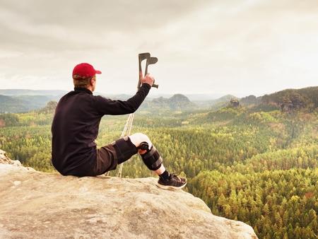 医療松葉杖で疲れて痛い観光。露出した岩の頂上で休んで膝ブレース機能に足の骨折の男。黒のスエットと赤い野球帽の男に座ってバレー怒鳴る。