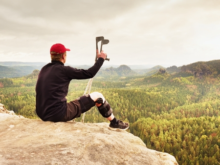 Tired hurt tourist with medicine crutches. Man with  broken leg in knee brace features resting on  exposed rocky summit. Valley bellow sitting man in black sweatshirt and red baseball cap. Sharp sandstone edge. Imagens