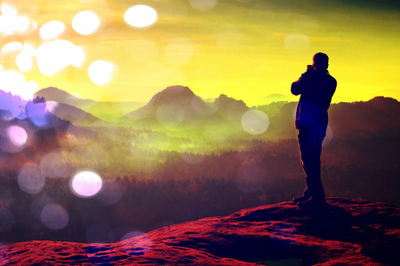 Film grain effect. Photographer takes photos with big camera on peak of rock. Dreamy misty landscape, hot Sun above
