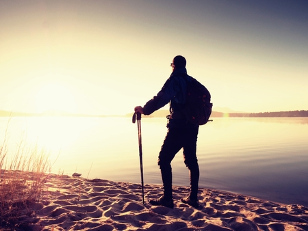 Man tourist with a backpack and trekking poles standing on sandy beach. Hiker enjoy empty beautiful beach in sunrise time.
