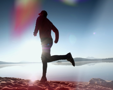 Leakage of light in the lens. Running man. Sportsman run, jogging guy during the sunrise above sandy beach. Damaged photo effect. Stock Photo
