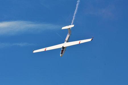 航空ショー: Memorial Airshow, 24th of June 2017, Roudnice, Czech Republic. Flying Glider aerobatic team withlight sailplane showing his performance, smoke effect 報道画像