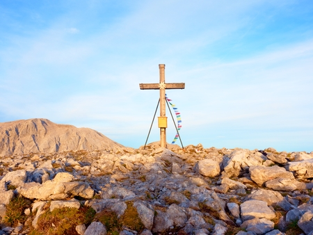 Big cross on top of  mountain as typical in the Alps. Wooden cross at mountain peak with Buddhist praying flags flutter in strong wind. Monument to victims of Alps Stock Photo