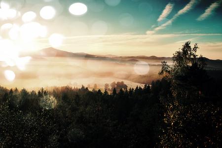 Efekt filmového zrna. Amazing daybreak v parku Saského Švýcarska. Pískovcové vrcholy rostly z mlhavého pozadí